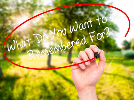 remembered: Man Hand writing What Do You Want to be Remembered For? with black marker on visual screen. Isolated on nature. Business, technology, internet concept. Stock Photo