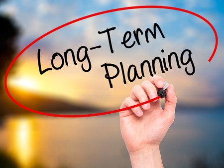 longterm: Man Hand writing  Long-Term Planning with black marker on visual screen. Isolated on background. Business, technology, internet concept. Stock Photo Stock Photo