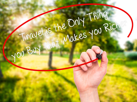 richer: Man Hand writing Travel is the Only Thing you Buy that Makes you Richer with black marker on visual screen. Isolated on nature. Business, technology, internet concept. Stock Photo