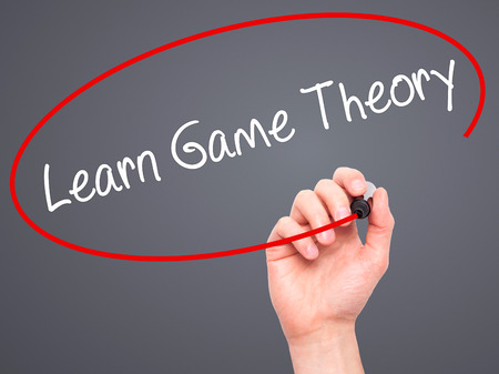 basic scheme: Man Hand writing Learn Game Theory with black marker on visual screen. Isolated on background. Business, technology, internet concept. Stock Photo Stock Photo