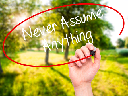 prudent: Man Hand writing Never Assume Anything with black marker on visual screen. Isolated on nature. Business, technology, internet concept. Stock Photo