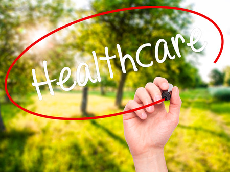 Man Hand writing Healthcare with black marker on visual screen. Isolated on nature. Business, technology, internet concept. Stock Photo Stock Photo