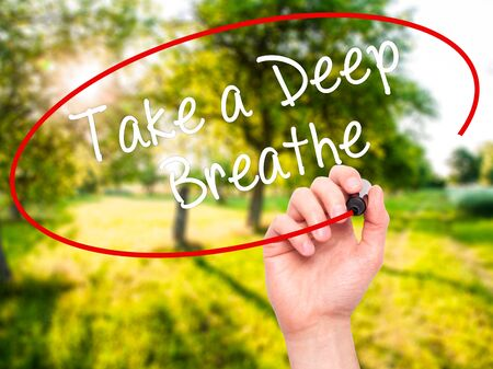 Man Hand writing Take a Deep Breathe with black marker on visual screen. Isolated on nature. Business, technology, internet concept. Stock Photo