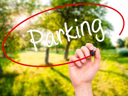 multi story car park: Man Hand writing Parking with black marker on visual screen. Isolated on nature. Business, technology, internet concept. Stock Photo