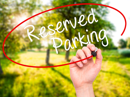 vacant sign: Man Hand writing Reserved Parking with black marker on visual screen. Isolated on nature. Business, technology, internet concept. Stock Photo