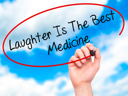 Man Hand writing Laughter Is The Best Medicine  with black marker on visual screen. Isolated on sky. Business, technology, internet concept. Stock Photo