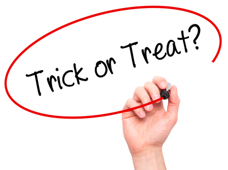 Man Hand writing Trick or Treat? with black marker on visual screen. Isolated on background. Business, technology, internet concept. Stock Photo