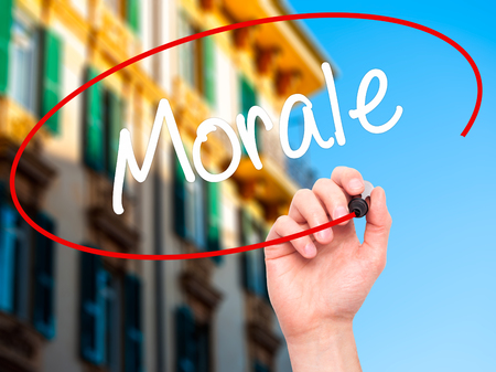 normative: Man Hand writing Morale with black marker on visual screen. Isolated on city. Business, technology, internet concept. Stock Photo