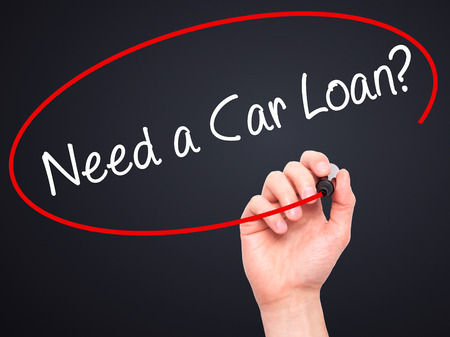 buying questions: Man Hand writing Need a Car Loan? with black marker on visual screen. Isolated on black. Business, technology, internet concept. Stock Photo