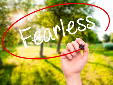 fearless: Man Hand writing Fearless  with black marker on visual screen. Isolated on background. Business, technology, internet concept. Stock Photo Stock Photo