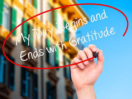 begins: Man Hand writing My Day Begins and Ends with Gratitude with black marker on visual screen. Isolated on city. Business, technology, internet concept. Stock Photo