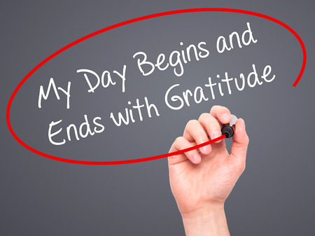 begins: Man Hand writing My Day Begins and Ends with Gratitude with black marker on visual screen. Isolated on grey. Business, technology, internet concept. Stock Photo