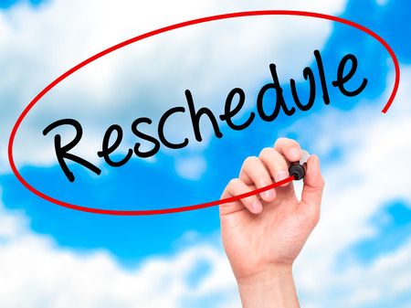 postpone: Man Hand writing Reschedule  with black marker on visual screen. Isolated on background. Business, technology, internet concept. Stock Photo