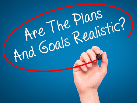 specific: Man Hand writing Are The Plans And Goals Realistic? with black marker on visual screen. Isolated on background. Business, technology, internet concept. Stock Photo Stock Photo