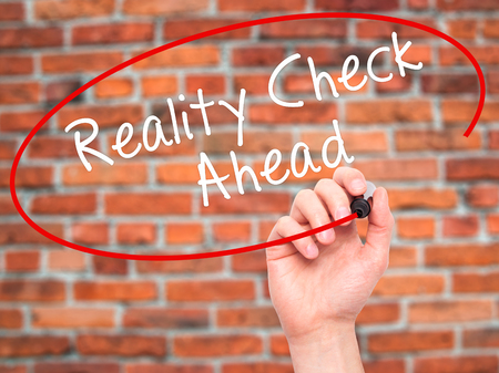 realism: Man Hand writing Reality Check Ahead with black marker on visual screen. Isolated on bricks. Business, technology, internet concept. Stock Photo