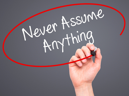 assume: Man Hand writing Never Assume Anything with black marker on visual screen. Isolated on grey. Business, technology, internet concept. Stock Photo