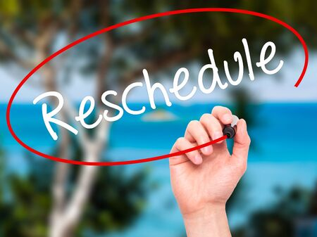 rescheduling: Man Hand writing Reschedule  with black marker on visual screen. Isolated on background. Business, technology, internet concept. Stock Photo