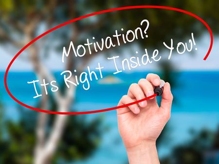 sarcastic: Man Hand writing Motivation? Its Right Inside You!  with black marker on visual screen. Isolated on nature. Business, technology, internet concept. Stock Photo