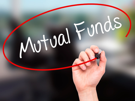 mutual funds: Man Hand writing Mutual Funds  with black marker on visual screen. Isolated on office. Business, technology, internet concept. Stock Photo