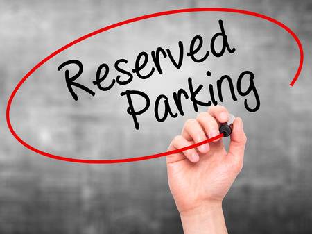 vacant sign: Man Hand writing Reserved Parking with black marker on visual screen. Isolated on grey. Business, technology, internet concept. Stock Photo