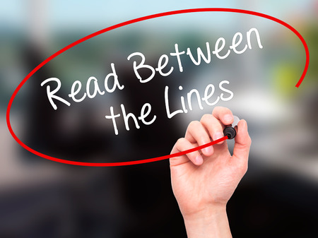 Man Hand writing Read Between the Lines   with black marker on visual screen. Isolated on office. Business, technology, internet concept. Stock Photo