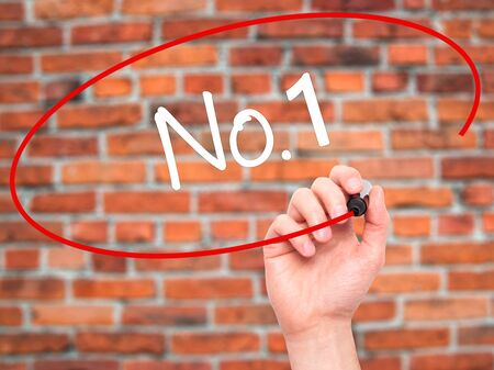 no1: Man Hand writing No.1 with black marker on visual screen. Isolated on bricks. Business, technology, internet concept. Stock Photo