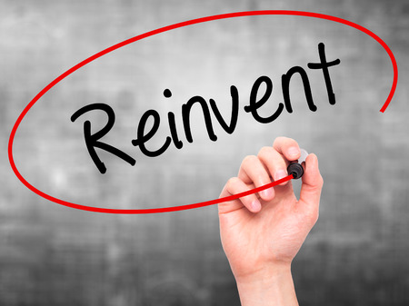 revitalize: Man Hand writing  Reinvent with black marker on visual screen. Isolated on background. Business, technology, internet concept. Stock Photo