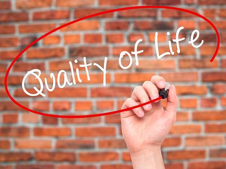 Man Hand schreiben Quality of Life mit schwarzen Marker auf visuellen Bildschirm. Isoliert auf Hintergrund. Wirtschaft, Technik, Internet-Konzept. Stockfoto