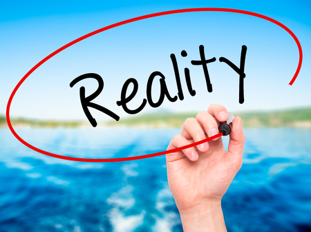 business skeptical: Man Hand writing  Reality with black marker on visual screen. Isolated on nature. Business, technology, internet concept. Stock Photo