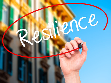 resilience: Man Hand writing Resilience with black marker on visual screen. Isolated on city. Business, technology, internet concept. Stock Photo