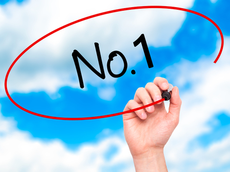 no1: Man Hand writing No.1 with black marker on visual screen. Isolated on sky. Business, technology, internet concept. Stock Photo