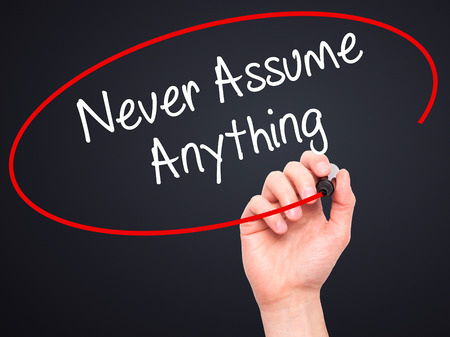 assume: Man Hand writing Never Assume Anything with black marker on visual screen. Isolated on black. Business, technology, internet concept. Stock Photo