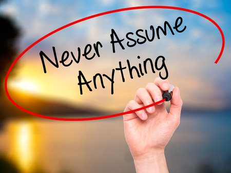 assume: Man Hand writing Never Assume Anything with black marker on visual screen. Isolated on nature. Business, technology, internet concept. Stock Photo