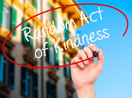 helpfulness: Man Hand writing Random Act of Kindness with black marker on visual screen. Isolated on city. Business, technology, internet concept. Stock Photo