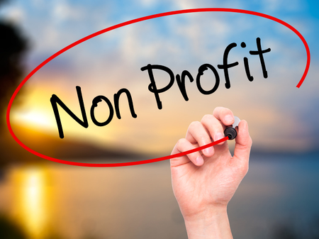 non profit: Man Hand writing Non Profit with black marker on visual screen. Isolated on nature. Business, technology, internet concept. Stock Photo