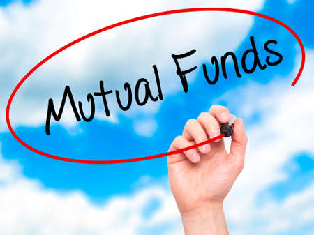 mutual funds: Man Hand writing Mutual Funds  with black marker on visual screen. Isolated on sky. Business, technology, internet concept. Stock Photo