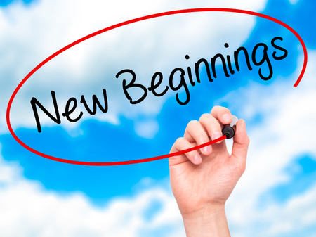 new beginnings: Man Hand writing New Beginnings with black marker on visual screen. Isolated on sky. Business, technology, internet concept. Stock Photo Stock Photo