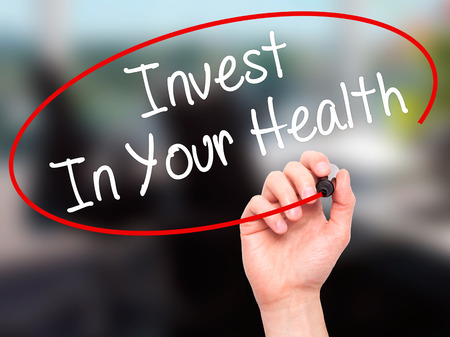 protecting your business: Man Hand writing Invest In Your Health with black marker on visual screen. Isolated on background. Business, technology, internet concept. Stock Photo