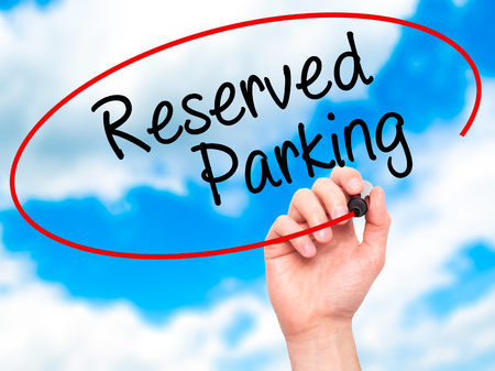 vacant sign: Man Hand writing Reserved Parking with black marker on visual screen. Isolated on sky. Business, technology, internet concept. Stock Photo Stock Photo