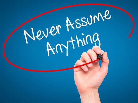 assume: Man Hand writing Never Assume Anything with black marker on visual screen. Isolated on blue. Business, technology, internet concept. Stock Photo