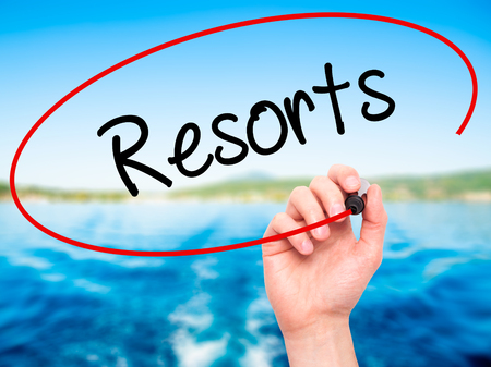 best guide: Man Hand writing Resorts  with black marker on visual screen. Isolated on background. Business, technology, internet concept. Stock Photo