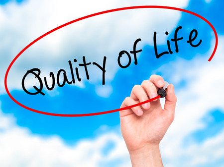 the good life: Man Hand writing Quality of Life with black marker on visual screen. Isolated on background. Business, technology, internet concept. Stock Photo