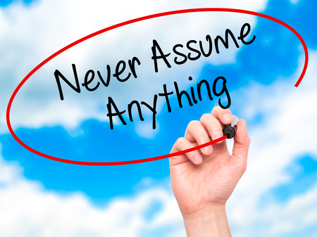 assume: Man Hand writing Never Assume Anything with black marker on visual screen. Isolated on sky. Business, technology, internet concept. Stock Photo