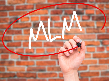 multilevel: Man Hand writing  MLM (Multi-Level Marketing) with black marker on visual screen. Isolated on background. Business, technology, internet concept. Stock Photo