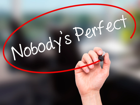 perfectionist: Man Hand writing Nobodys Perfect with black marker on visual screen. Isolated on background. Business, technology, internet concept. Stock Photo