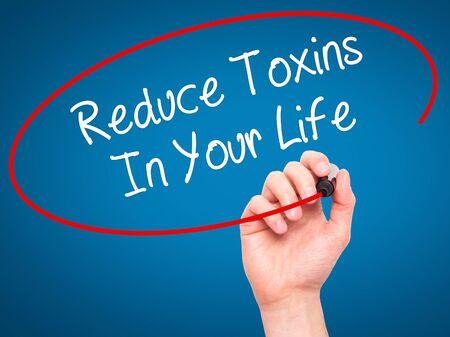 hombre escribiendo: Hombre de la mano escribiendo reducir las toxinas en su vida con marcador negro en la pantalla visual. Aislado en azul. Negocios, la tecnología, el concepto de internet. Foto de stock