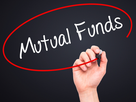 mutual funds: Man Hand writing Mutual Funds  with black marker on visual screen. Isolated on black. Business, technology, internet concept. Stock Photo