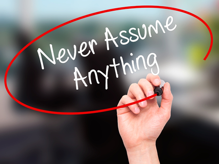 assume: Man Hand writing Never Assume Anything with black marker on visual screen. Isolated on office. Business, technology, internet concept. Stock Photo