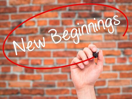 new beginnings: Man Hand writing New Beginnings with black marker on visual screen. Isolated on bricks. Business, technology, internet concept. Stock Photo