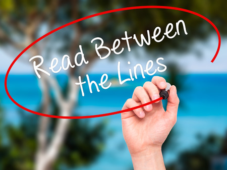 explicitly: Man Hand writing Read Between the Lines   with black marker on visual screen. Isolated on nature. Business, technology, internet concept. Stock Photo